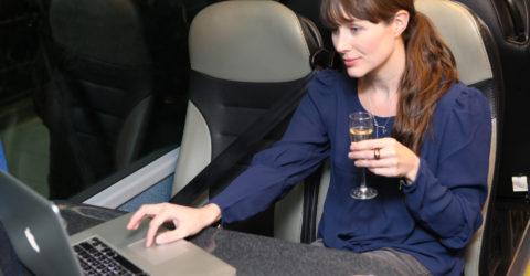 Young woman enjoying a glass of champagne whilst using a laptop on the Davian VIP coach